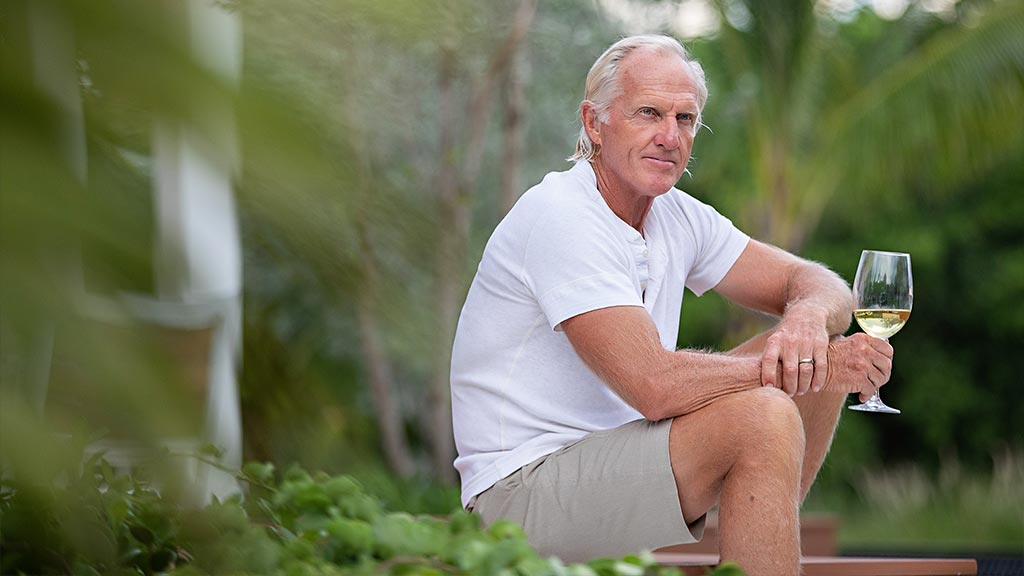 Greg Norman on the beach with glass of white wine